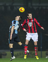 Matt Bloomfield of Wycombe goes up for the ball with Jamie Devitt of Morecambe during the Sky Bet League 2 match between Wycombe Wanderers and Morecambe at Adams Park, High Wycombe, England on 2 January 2016. Photo by Andy Rowland / PRiME Media Images