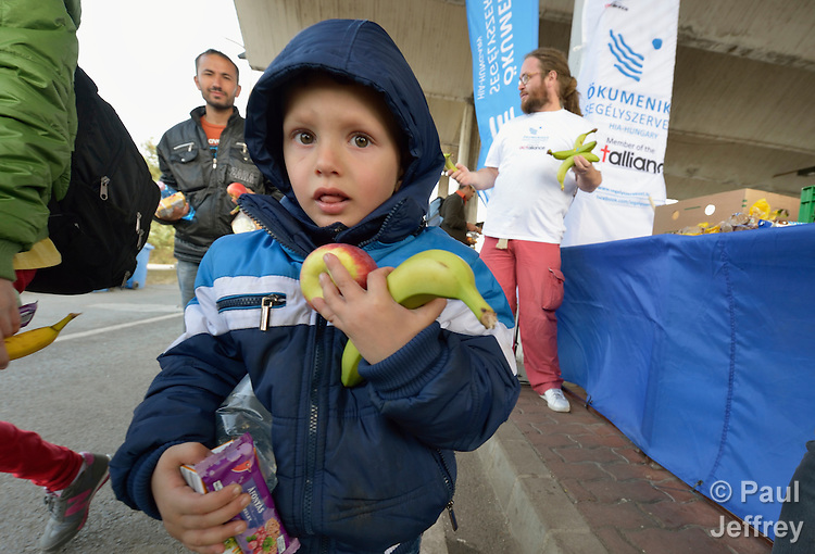 A refugee child holds fruit he received from the ACT Alliance at the border crossing into Austria near the Hungarian town of Hegyeshalom. Hundreds of thousands of refugees and migrants--including many children--flowed through Hungary in 2015, on their way to western Europe from Syria, Iraq and other countries. The ACT Alliance has provided food and other critical support for refugee and migrant families here and in other places along their journey.