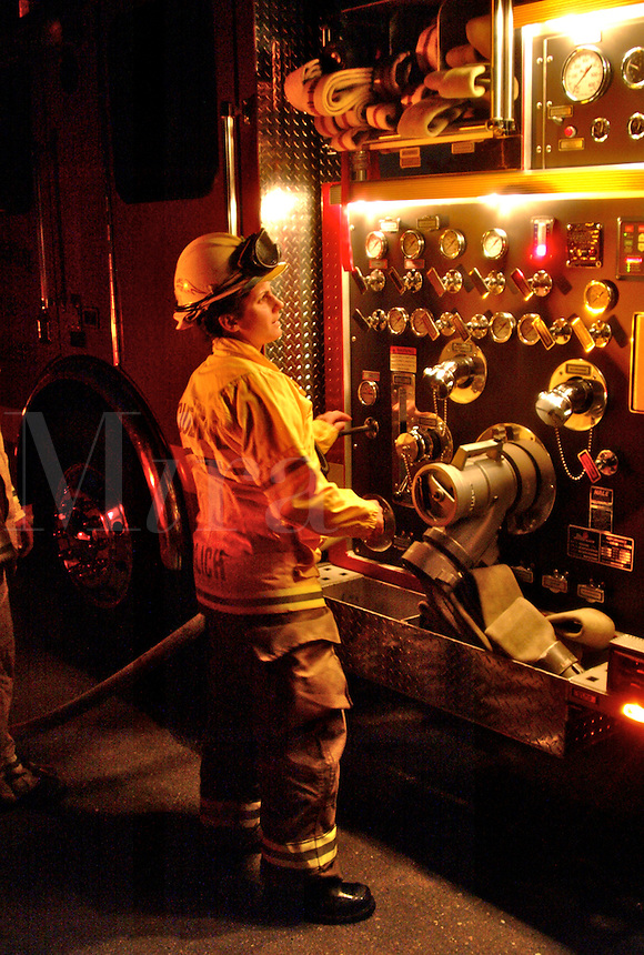 A female firefighter engineer operates the pump panel at a night time vegetation fire in Occidental California