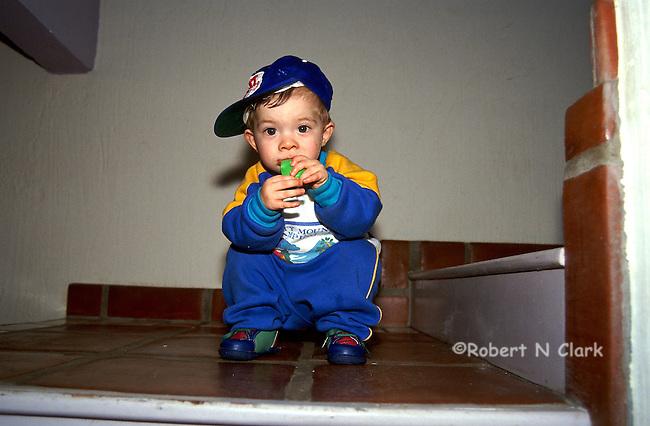 Boy in sweatsuit sitting on tile steps with hat bill turned sideways
