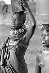 Turkana woman collecting water from a borehole and  carrying the load back to her village over 1 km away.<br /> Northern Kenya.