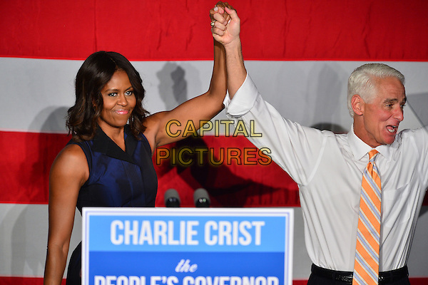 MIAMI GARDENS, FL - OCTOBER 17: First Lady Michelle Obama stands with former Florida Governor and now Democratic gubernatorial candidate Charlie Crist as she campaigns for him during an event at the Betty T. Ferguson Recreational Complex Gymnasium on October 17, 2014 in Miami Gardens, Florida. Crist is facing off against incumbent Republican Governor Rick Scott in the November 4, 2014 election  <br /> CAP/MPI10<br /> &copy;mpi10/MediaPunch/Capital Pictures