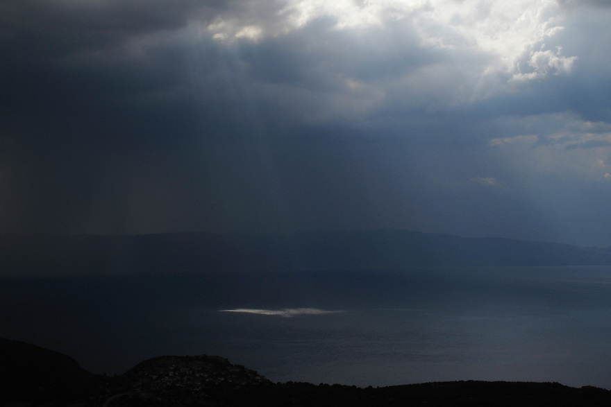Sunbeams, Rays of Buddha, Ropes of Maui, sun-drawing-water or Crepuscular rays break through thunder clouds travelling over Lake Ohrid. View west over Lake Ohrid towards Mokra Pl mountain range in Albania.<br /> Galicica National Park, Macedonia, June 2009<br /> Mission: Macedonia, Lake Macro Prespa /  Lake Ohrid, Transnational Park<br /> David Maitland / Wild Wonders of Europe
