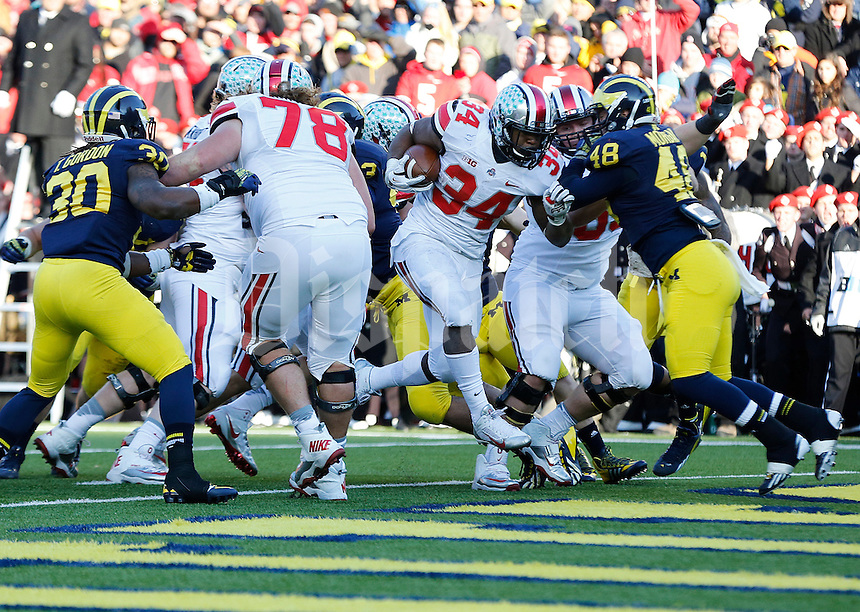 Ohio State Buckeyes running back Carlos Hyde (34) rushes for the team's final touchdown in the fourth quarter of the college football game between the Ohio State Buckeyes and the Michigan Wolverines at Michigan Stadium in Ann Arbor, Michigan Saturday afternoon, November 30, 2013. The Ohio State Buckeyes defeated the Michigan Wolverines 42 - 41. (The Columbus Dispatch / Eamon Queeney)