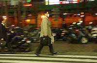 A businessman rushes through the Shinjuku district of Tokyo..Mar 2002