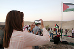 A Palestinian woman take a photo by a phone to the Palestinian flag at the Bedouin village of Khan al-Ahmar, in the occupied West Bank against Israel's plan to demolish the village on September 26, 2018. Photo by Shadi Hatem