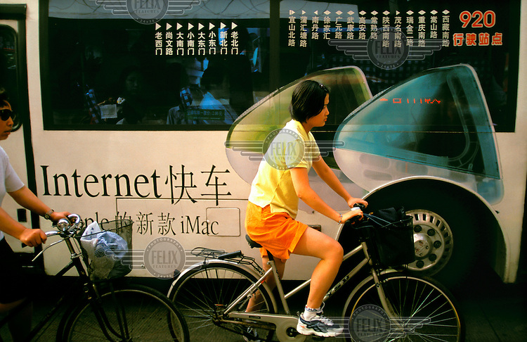 Mark Henley / Panos Pictures..China, Shanghai..Westernisation. Cyclists passing advertising for Apple Macintosh computers, stressing ease of connection to internet with iMac models...