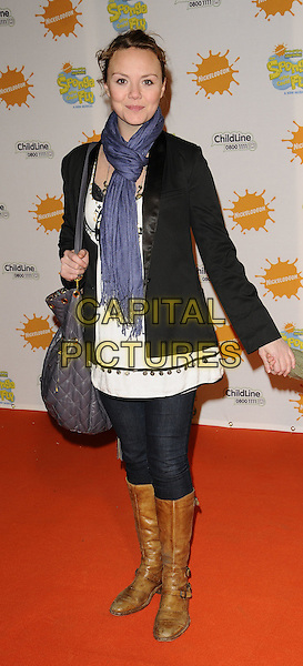 "CHARLIE BROOKS & GUEST.At the ""Spongebob Squarepants - The Sponge who could Fly"" Gala performance at the Hammersmith Apollo, London, England. .March 5th 2009 .full length black leather jacket brown boots grey gray bag purse blue scarf white .CAP/CAN.©Can Nguyen/Capital Pictures."