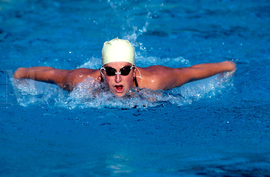 A female competitive swimmer does the butterfly stroke.