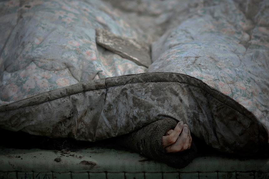 The body of a victim is covered with a blanket after it was retrieved from the rubbles of Rikuzentakat days after the area was devastated by a magnitude 9.0 earthquake and tsunami March 17, 2011.   REUTERS/Damir Sagolj (JAPAN)