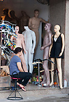 Hanoi, Vietnam, A woman sits motionless amongst her mannequins.photo taken July 2008.