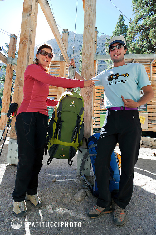 Two hikers laughing while weighing their big backpacks before heading in to climb Mt. Whitney. Sierra Nevada, California