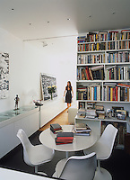 Home owner Emma Shapero walking towards an enclosed library located off the open plan living area