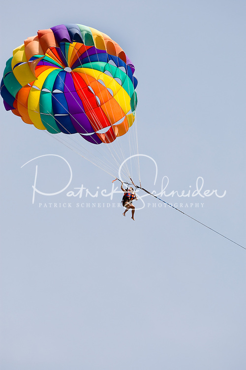 A woman parasails beneath a rainbow colored parasail over Playa la Ropa Beach in Zihuatanejo, Mexico.  (taken August 2007). Photo by Patrick Schneider Photo.com