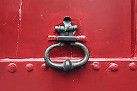 A brightly-colored red door and ornate knocker, France.