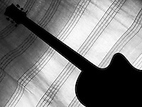 """Black & white fine art still life photo of guitar silhouette with curtain on background having staff like patterns on it.<br /> <br /> To view the same image in color visit the gallery-""""Food & Other Still Life""""."""