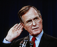 ***FILE PHOTO*** George H.W. Bush Has Passed Away<br /> Washington, DC., USA,  1991<br /> President George H.W. Bush holds his hand to his ear trying to hear a question during a press conference in the East Room of the White House. <br /> CAP/MPI/MRN<br /> &copy;MRN/MPI/Capital Pictures