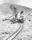 Double-headed K class locomotives eastbound with and empty pipe train.  Coming around a hill and over a small timber trestle.  Highway in background.<br /> D&amp;RGW  e. of Monero, NM