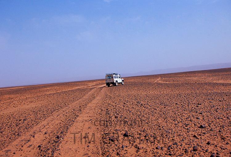 White Land Rover crossing the stony desert floor leaving a dust trail behind in the Sahara Desert, Morocco