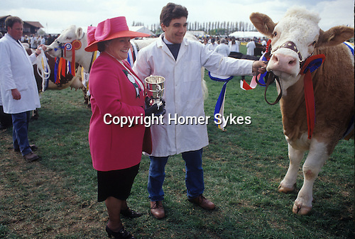 Newark, Nottinghamshire, England. Nottingham county show takes place annually during the summer. Mrs. Rachael Gascoigne wearing a new matching pink suit and hat presents a prize of a silver cup to the owner of the much decorated heifer adorned with class winners rosettes.
