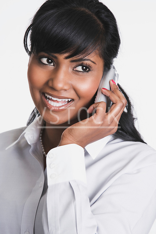 Businesswoman talking on mobile phone in studio