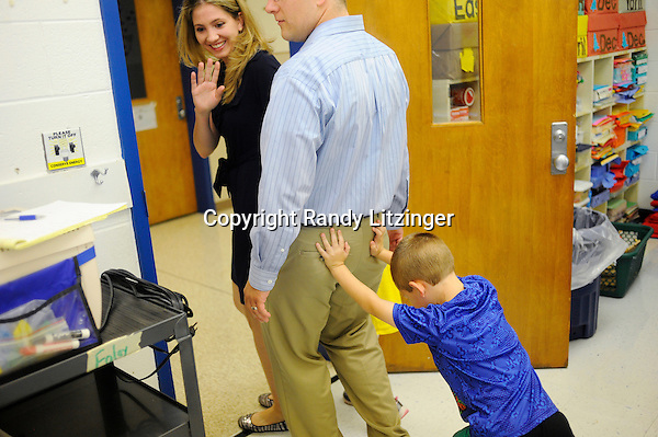 Kindergartener Zander Simmons pushes his mom Kelly and dad Chris out the door after they visited his classroom for the first couple minutes of his first ever day of school at H.M. Pearson Elementary school in Catlett.<br />