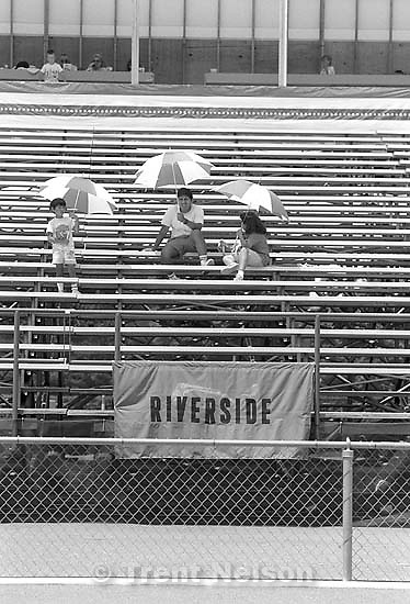 People in stands with parasols at Special Olympics.<br />
