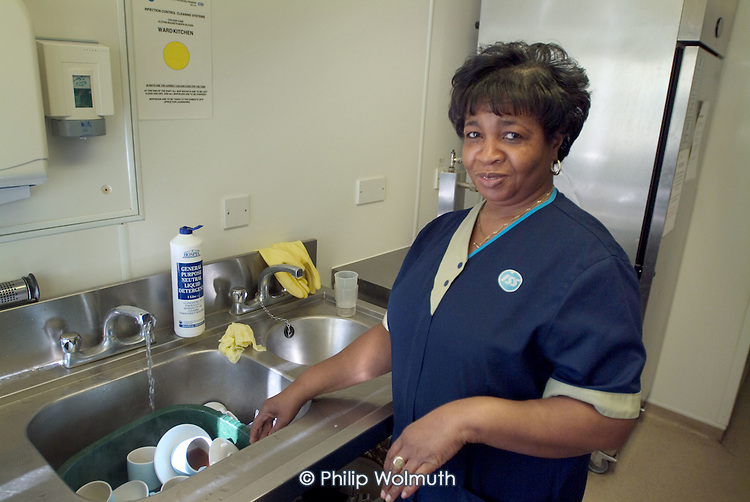 A domestic washes dishes on a ward at Homerton Hospital, Hackney, east London, where threatened industrial action by UNISON members employed by multinational ISS Mediclean in catering, portering and cleaning services lead to a deal which took pay from £4.43 to £5.00 an hour (£5.35 from 1 April 2004),  improved annual leave and the introduction of an occupational sick pay scheme.  The claim was part of the Living Wage campaign carried out in partnership with the East London Citizens Organisation (TELCO).