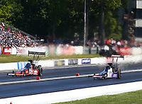 Jun. 1, 2014; Englishtown, NJ, USA; NHRA top fuel driver J.R. Todd (left) races alongside Leah Pritchett during the Summernationals at Raceway Park. Mandatory Credit: Mark J. Rebilas-