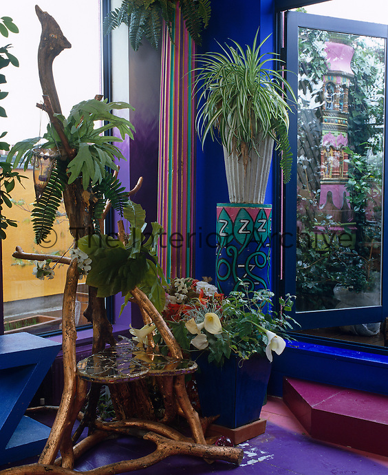 Lush houseplants in exotic planters in the corner of the living room by the French windows