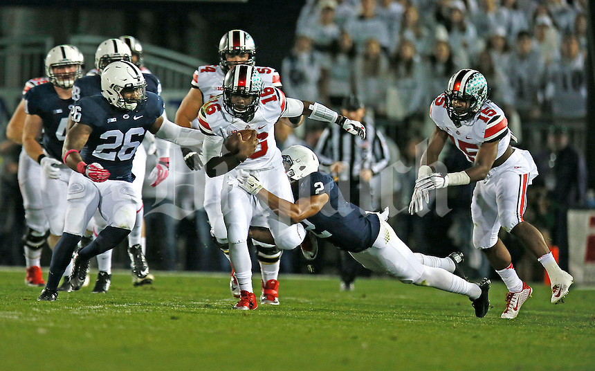 Ohio State Buckeyes quarterback J.T. Barrett (16) gains yardage in the first half at Beaver Stadium on October 25, 2014.  (Chris Russell/Dispatch Photo)