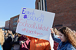 North Bellmore; New York; USA. March 14; 2018. Mepham High School students, protesting gun violence and some holding protest signs, walk out of class for 17 minutes; from 10:00 am to 10:17 am EST; one minute for each student shot and killed last month in a Parkland, Florida, high school. Protest sign message: Enough is #ENOUGH, School Walkout, #NeverAgain. This was part of a nationwide walkout in soildarity with student shooting victims, and a demand for U.S. laws to reduce gun violence.