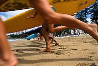 Surfers running into the surf on Bondi Beach, Australia.
