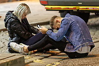 Pictured: Two young revellers sit on the road surface in Wind Street, Swansea. Monday 31 December 2018 and Tuesday 01 January 2019<br /> Re: New Year revellers in Wind Street, Swansea, Wales, UK
