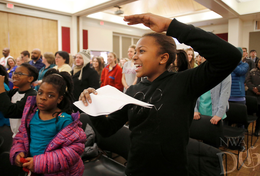 NWA Democrat-Gazette/DAVID GOTTSCHALK  Alexis Fletcher, 12, participates in songs and chants Monday, January 18, 2016, led by Sandra Walton, a junior at the University of Arkansas, at the University of Arkansas in Fayetteville. The songs and chants were part of the Martin Luther King, Jr. Vigil and Freedom March celebration co-sponsored by the University of Arkansas Associated Student Government, the Black Student Association and the Northwest Arkansas Martin Luther King, Jr. Council.