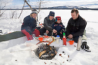 Sweden, SWE, Kiruna, 2006-Apr-16: Barbecue party in Lapland: a man, a four year old child and two women sitting on the banks of the frozen Holmajarvi lake grilling sausages.