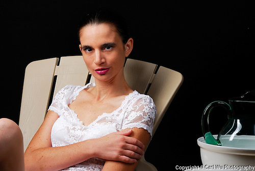 Model Wearing A White Lacy Blouse, White Bra, Sitting In A Beige Patio Chair, Next To A Side Table With Tureen And Green Glass Pitcher,  Wtih A Black Background