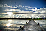 South Carolina Lowcountry sunset dock marsh grass scene HDR bright sun behind fluffy clouds puffy dock reflections