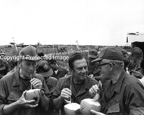Pausing for refreshments during their visit to Huu Thanh, a recently pacified village, three U.S. Senators on President Nixon's fact-finding committee drink from local coconuts.  Thomas J. McIntyre, Howard Cannon, and George Murphy.  Ca. 1970. (USIA)<br /> EXACT DATE SHOT UNKNOWN<br /> NARA FILE #:  306-MVP-18-13<br /> WAR & CONFLICT BOOK #:  389