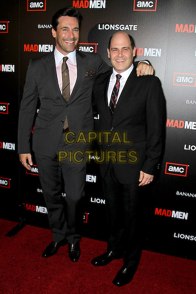 """JON HAMM, MATTHEW WEINER.at the Season 4 premiere of AMC's """"Mad Men"""", Mann Chinese 6 Theatre. Hollywood, CA, USA, July 20th, 2010. .full length black tie pink white collar shirt grey gray smiling brown arm around .CAP/CEL.©CelPh/Capital Pictures."""