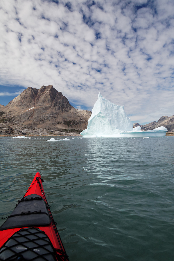 Bow of sea kayak with pinnacled iceberg and mountains, Sammileq Fjord, Ammassalik Island, East Greenland