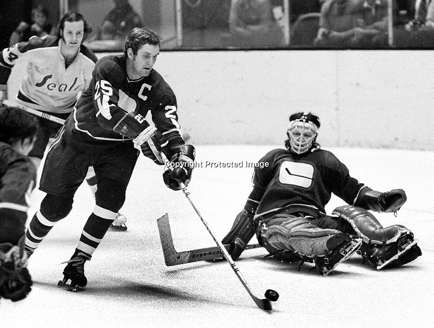 Vancouver Canucks, vs the California Golden Seals. #25 Orland Kurtenbach grabs puck to help goalie Dune Wilson. (1972 photo/Ron Riesterer)