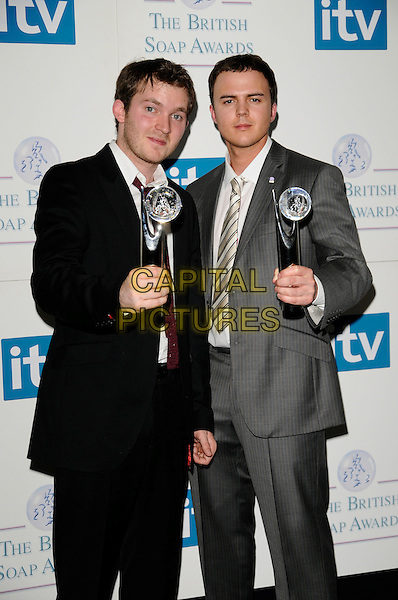 MATT LITLER & DAREN JON-JEFFRIES .of Hollyoaks.Attending the British Soap Awards 2008.BBC Television Centre, Wood Lane, London, England, 3rd May 2008.press room half length winners black suit grey gray red tie awards trophies .CAP/CAN.© Can Nguyen/Capital Pictures
