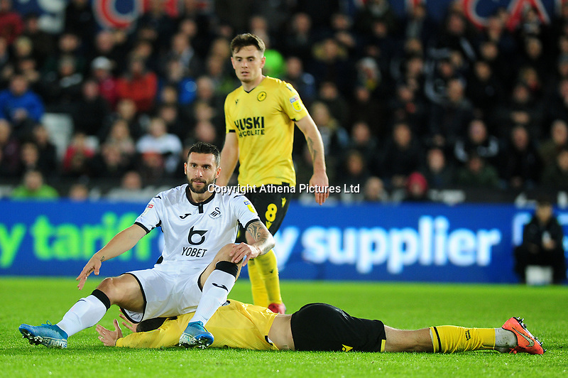 Borja Baston of Swansea City sits on Jake Cooper of Millwall during the Sky Bet Championship match between Swansea City and Millwall at the Liberty Stadium in Swansea, Wales, UK. Saturday 23rd November 2019