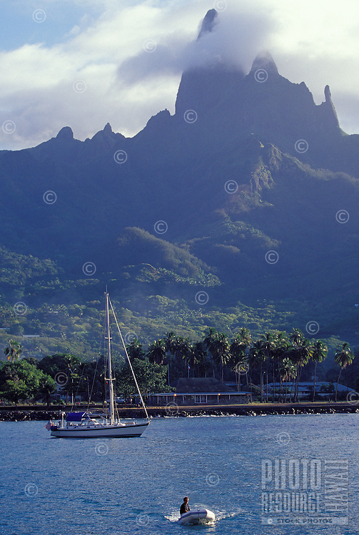 Man riding dinghy to shore from sailing yacht 'Heron', at anchor off dramatic cliff peaks of Ua Pou Island, Marquesas, French Polynesia