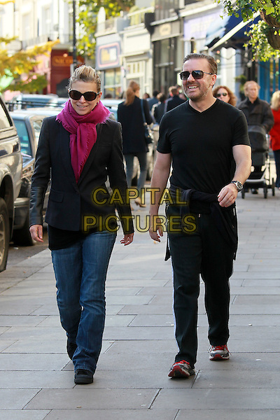 Jane Fallon & Ricky Gervais.Spotted strolling in Primrose Hill, North.London, England, UK, .October 29th 2011..couple full length walking pink scarf black t-shirt sunglasses jeans jacket smiling jumper tied around waist trousers partner girlfriend .CAP/HIL.©John Hillcoat/Capital Pictures.