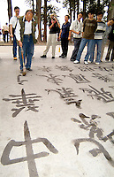 China Beijing man in park practicing writing Chinese Calligraphy in Beijing China