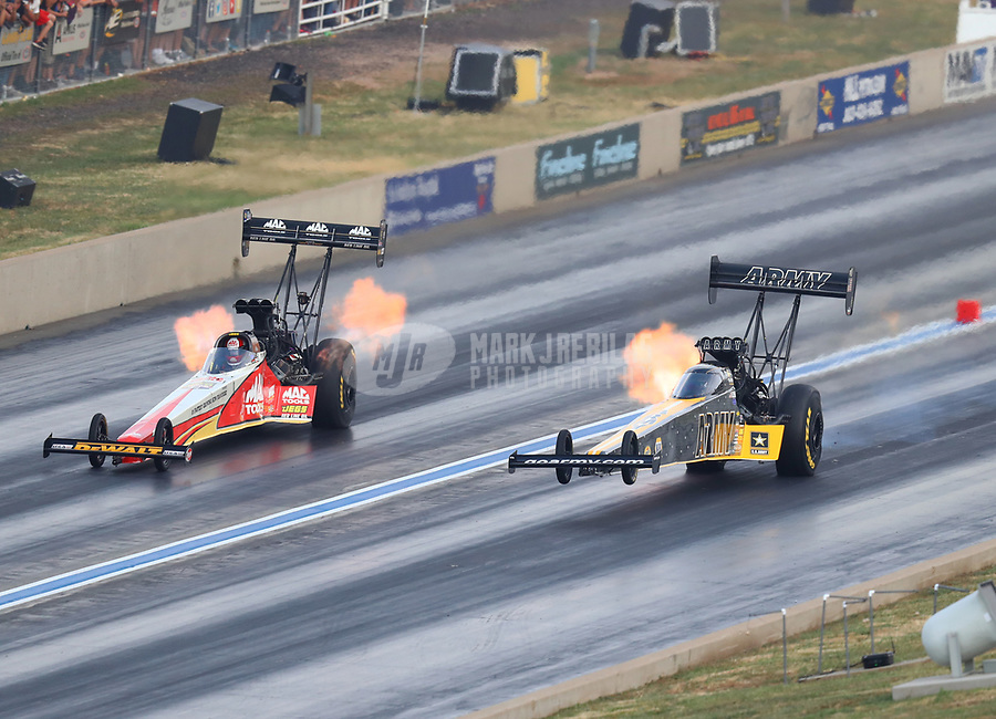 Jul 22, 2017; Morrison, CO, USA; NHRA top fuel driver Doug Kalitta (left) races alongside Tony Schumacher as he does a wheelstand during qualifying for the Mile High Nationals at Bandimere Speedway. Mandatory Credit: Mark J. Rebilas-USA TODAY Sports
