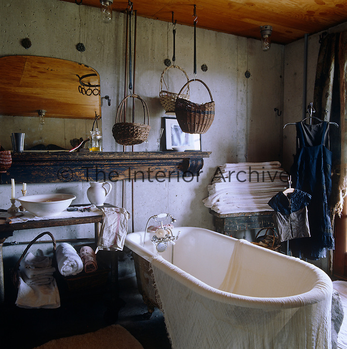 The old-fashioned bathroom is furnished with a jug and basin on a wooden washstand and a roll-top bath