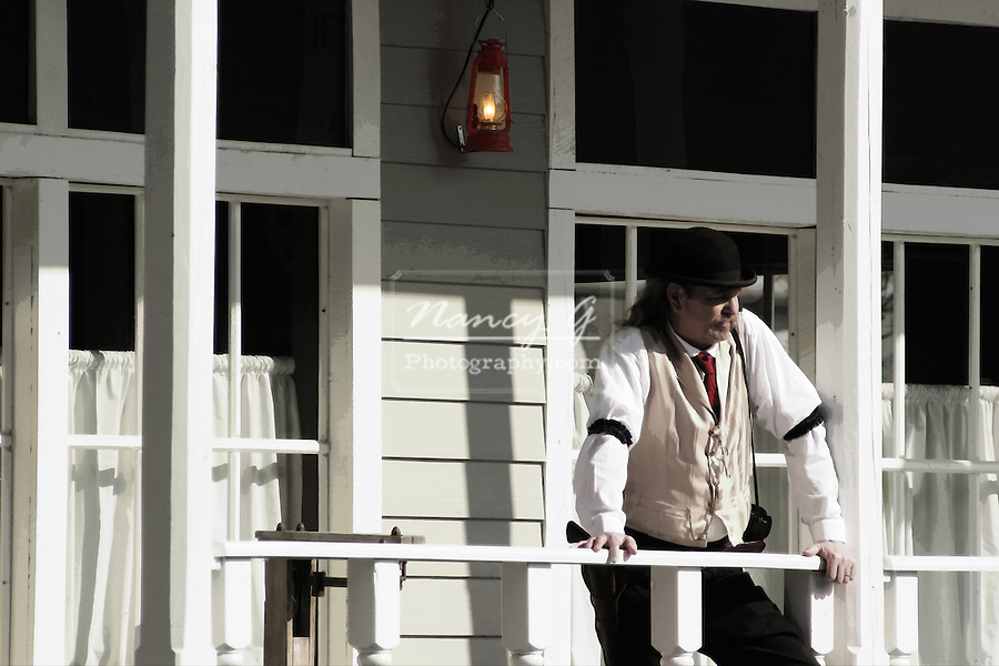 A bar tender from the old western building is outside on the porch taking a break  Red tie and lantern digital color